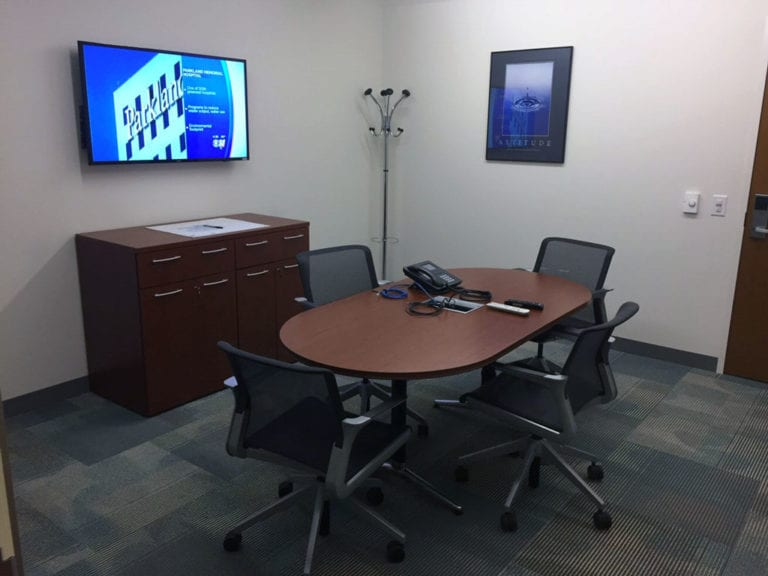 Small huddle room with video display and conference phone.