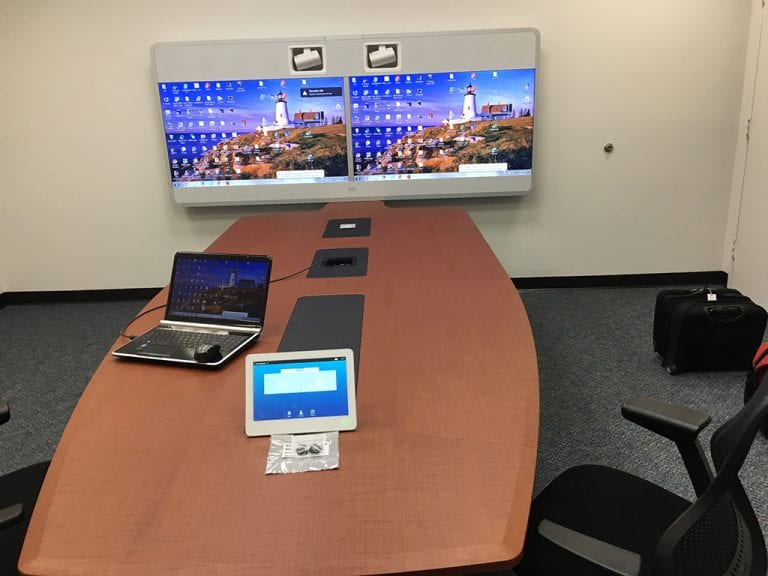 Conference room with medium size dual display video conference system at the end of the table.
