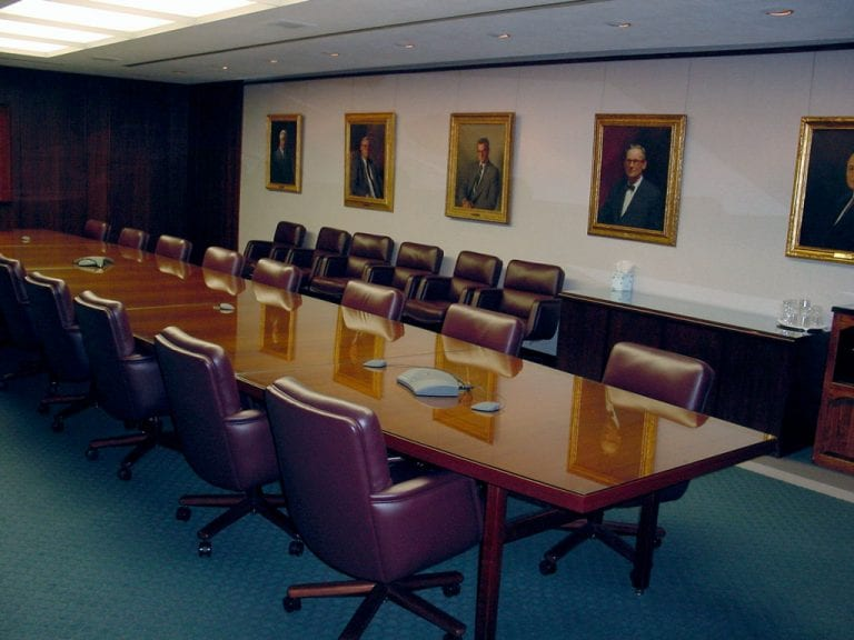 Boardroom at a bank featuring a conference phone and a video screen tastefully enclosed in a wooden cover to blend with the traditional decor.