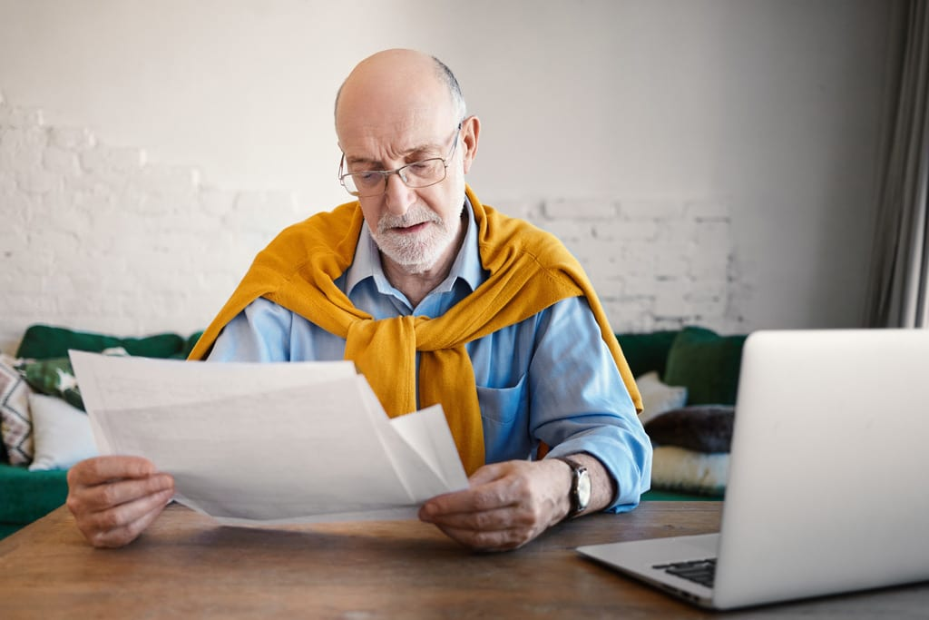 Man with Glasses Reviewing Papers with a Computer