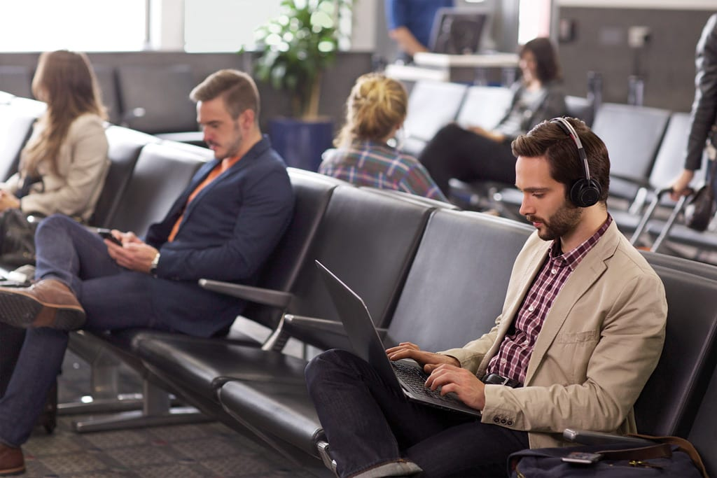 Man Working Remotely at an Airport with Poly Voyager